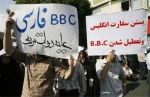 Pro-Ahmadinejad supporters hold up anti-BBC slogans in Tehran (AFP)